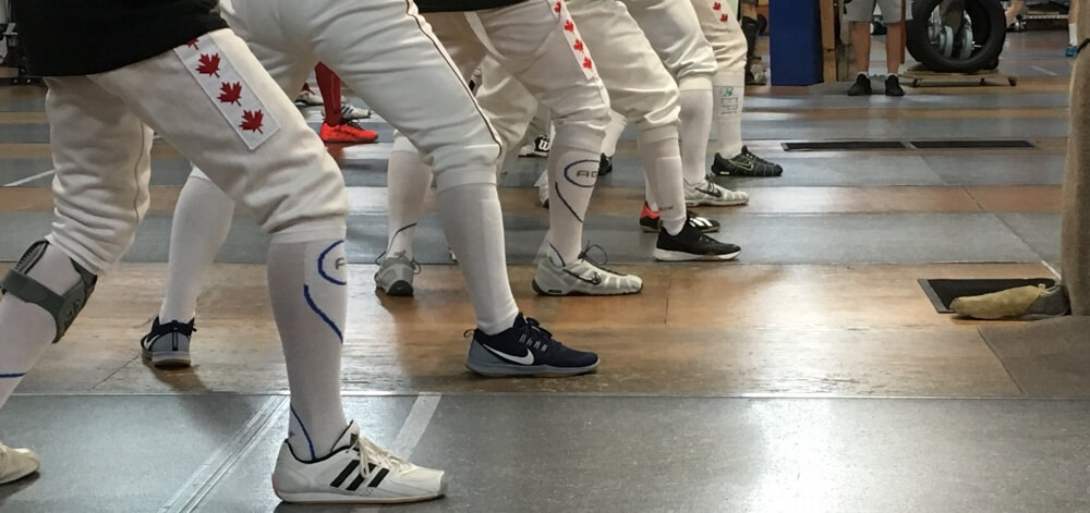 Row of fencers standing in en guarde from the view of their feet